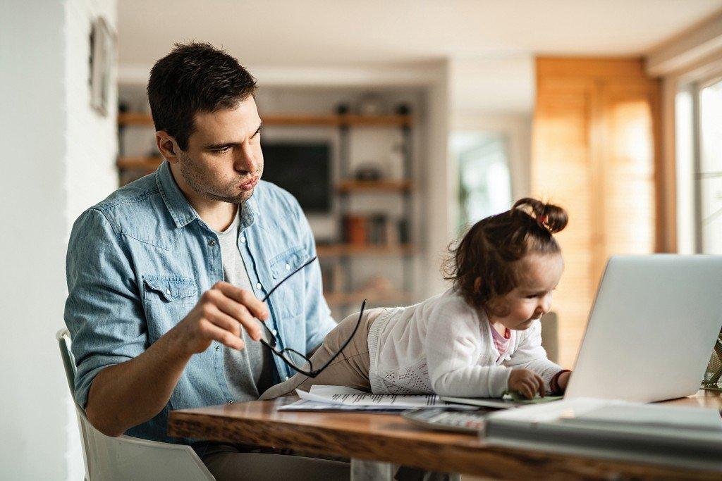 Hombre trabajando en casa con una bebé