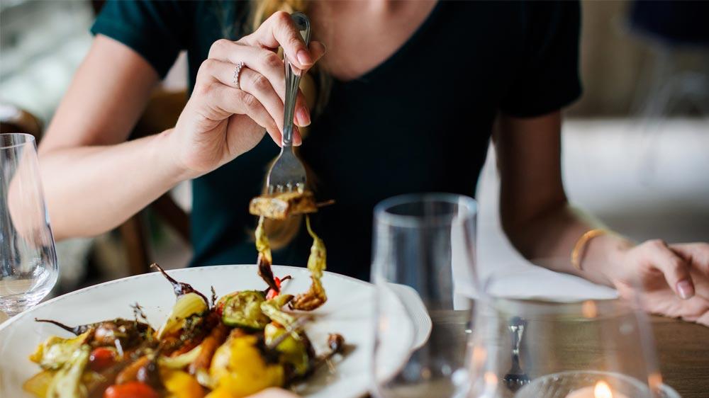 Mujer comiendo pasta en un restaurante